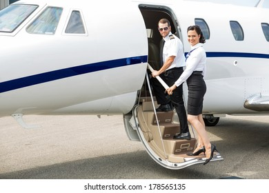 Portrait of stewardess and pilot boarding private jet