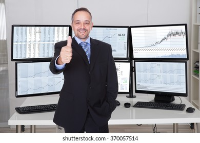 Portrait of stock market broker gesturing thumbs up against multiple monitors in office
