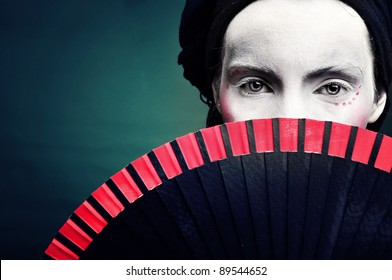 portrait of a strange woman mime or a clown with a fan and bodypainting