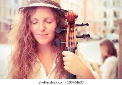 Portrait of street musician woman with cello closed eyes. Split toning
