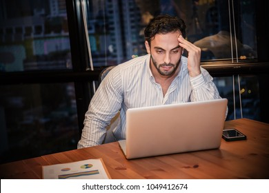 Portrait of stress sad business man working late at night time in office. Business man work hard lifestyle stress burnout overtime office syndrome concept.