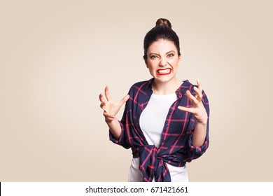 Portrait of stressed and annoyed young casual styled caucasian woman with hair bun holding hands in mad furious gesture, screaming with ragea nd anger. Negative human emotions, facial expressions