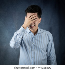 Portrait stressed and anxiety handsome young asian man wearing a blue shirt isolated on black wall background.  Asia people.