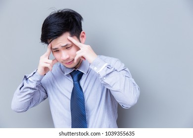 Portrait stressed businessman: Attractive guy gets headache because charming handsome business man work too hard and get stressed or asian guy get office syndrome that makes him painful, copy space