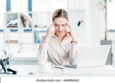 portrait of stressed businesswoman sitting at workplace in modern office