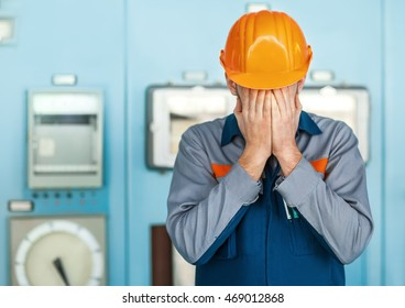 Portrait of stressed despair engineer closed face by two hands