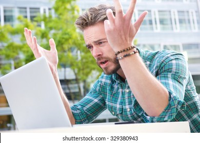 Portrait of a stressed man looking at laptop with hands raised