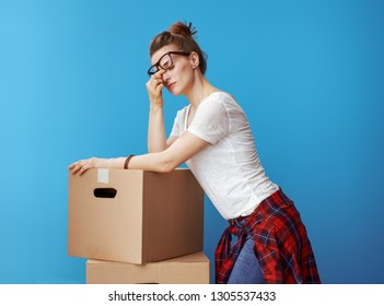 Portrait of stressed modern woman in white t-shirt near cardboard boxes on blue background
