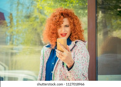 Portrait of stressed office young frustrated woman holding cellphone in hand on the city street in summer, looking at screen with cross face expression, mad at stressful texts and calls