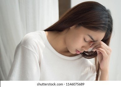 portrait of stressed sick woman with headache; depressed woman suffers from vertigo, dizziness, migraine, hangover; health care concept; 20s young adult asian middle east, mixed race woman model