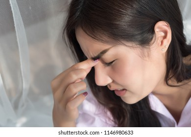 portrait of stressed sick woman with headache; depressed woman suffers from vertigo, dizziness, migraine, hangover; health care and mental health concept; 20s young adult asian woman model