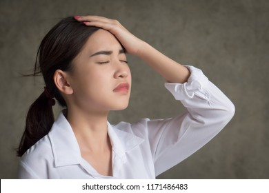 portrait of stressed and sick woman with headache; ill woman suffers from stress, vertigo, dizziness, migraine, hangover, health care concept; young adult asian woman model