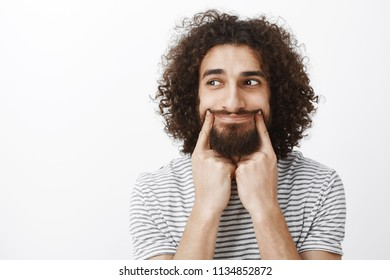 Portrait of stressed upset attractive bearded man with curly hair, pulling smile with index finger and looking left with sad expressions, being bored, having nothing to do after friends went home