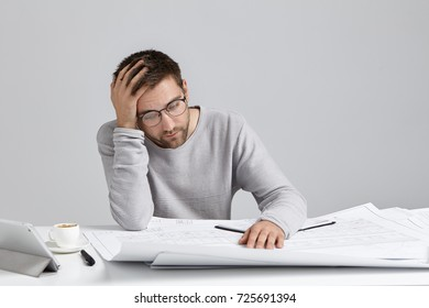 Portrait of stressed young Caucasian architect holding hand on head and looking at blueprints in front of him, having desperate and hopeless expression, feeling absolutely exhausted and worn out