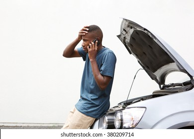 Portrait of stressed young man calling on cellphone for service his breakdown car