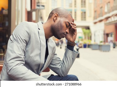 Portrait stressed young man hands on head with bad headache isolated city street background. Negative human emotion facial expression feeling