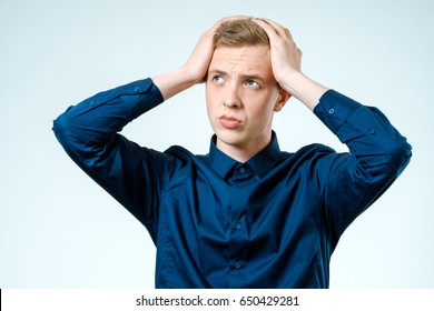 Portrait of stressed young man, hands on head. Isolated background. Negative human emotion and facial expression.