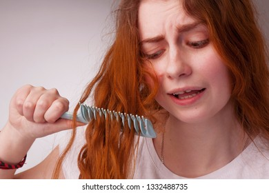 Portrait of a stressed young woman with tousled and disheveled long hair want to comb her hair. Beauty concept.