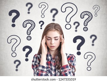 Portrait of stressed young woman wearing checkered shirt and having a headache sitting near concrete wall with many question marks drawn on it.