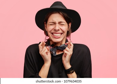 Portrait of stressful annoyed female clenches teeth and crosses fingers in anticipation, has desperate expression, wears stylish black hat, poses against pink background. Please let`s dreams come true