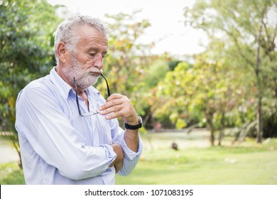 Portrait of stressful sad senior caucasian old man in the park outdoors with copy space. Spring healthcare lifestyle stress painful retirement golden age crisis concept banner