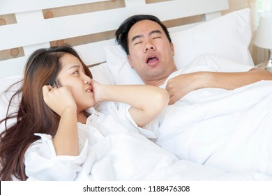Portrait of stressful or tired exhausted young Asian woman with man or couple snoring while sleeping in bedroom. healthy mental care medical and Obstructive sleep apnea and Snoring concept.