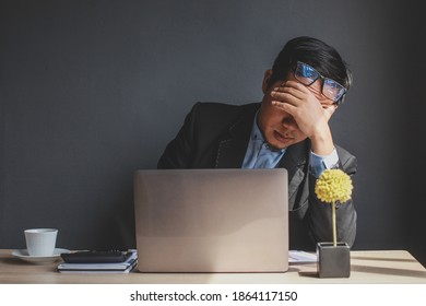 Portrait of stressful tired young asian businessman at work. Tired businessman feeling stressed, feels eye strain fatigue after long office work on laptop, overwork, office syndrome, business problem.
