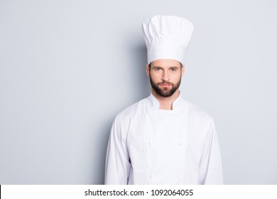 Portrait of strict confident chef cook with stubble in beret and white outfit looking at camera isolated on grey background