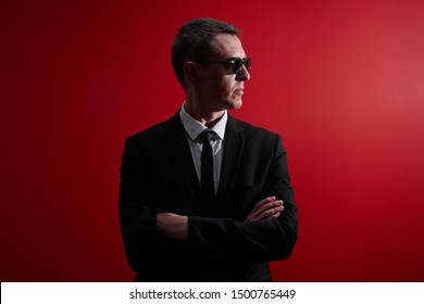 Portrait of strict serious adult man in suit and black glasses looks away with crossed arms on red studio background. Face control, night club security