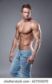 Porträt eines starken Athletic Fitness Mannes mit großen Muskeln auf grauem Hintergrund