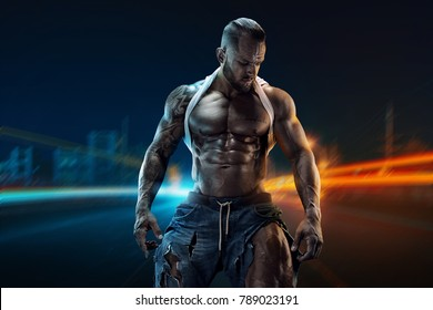 portrait of strong Athletic Fitness man showing big muscles over town background