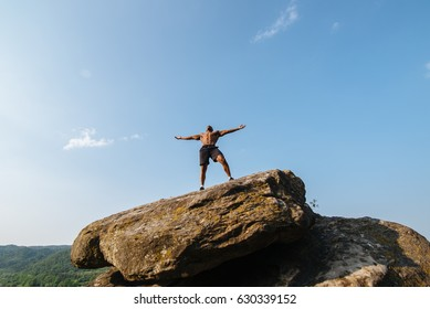 Portrait of strong black bodybuilder with naked torso posing on the rock. Blue cloudy sky background