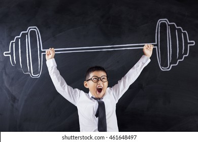 Portrait of a strong boy lifting dumbbell in the classroom, concept for strength and confidence to be success person