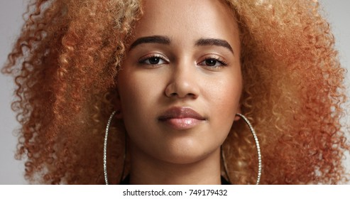 Portrait of a strong confident mixed race woman with reddish blond afro and large hoop earrings