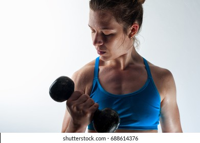 Portrait of strong confident woman with dumbbell. Fitness female working out with weight, looking to the biceps. White background.