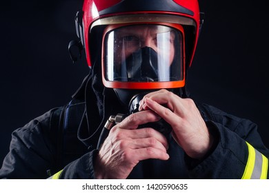 portrait strong fireman in fireproof uniform holding an ax chainsaw in his hands black background studio.oxygen mask on the head close up