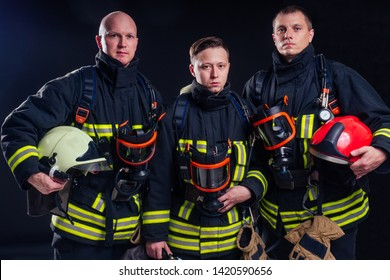 portrait еркуу strong fireman in fireproof uniform holding an ax chainsaw in his hands black background studio.team work concept