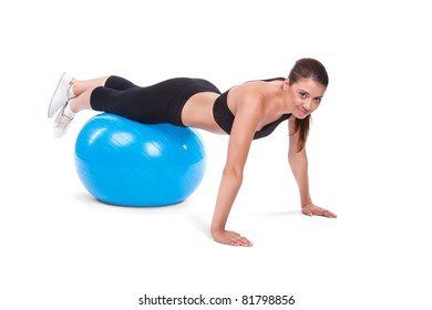 Portrait of strong girl excercising with fitball in gym