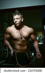 Portrait of a strong handsome guy posing. Bodybuilder