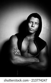 Portrait of a strong handsome guy posing in hood. Bodybuilder