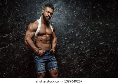 Portrait of strong healthy handsome Athletic Man Fitness Model posing near dark wall