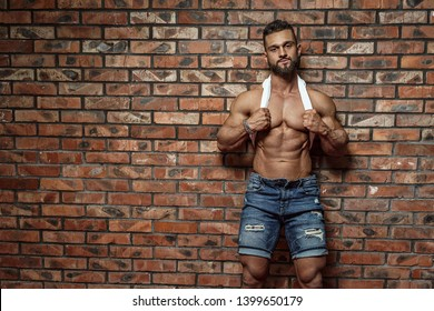 Portrait of strong healthy handsome Athletic Man Fitness Model posing near Brick wall