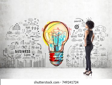 Portrait of a strong and independent African American woman wearing black and standing with her hands on the waist. Concrete wall with a business plan sketch and a large light bulb