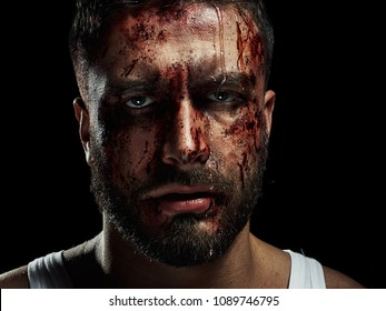 Portrait of a strong man with a beard, face in blood. He looks at the camera with different emotions. Blood and sweat dripping down his face. Fists erased from strikes