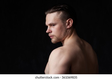 Portrait of a strong man with naked torso, profile