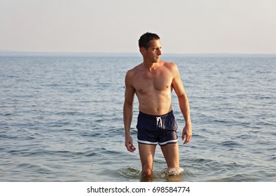 Portrait of Strong muscular Man on the beach, perfect body, abs, six pack, sea,