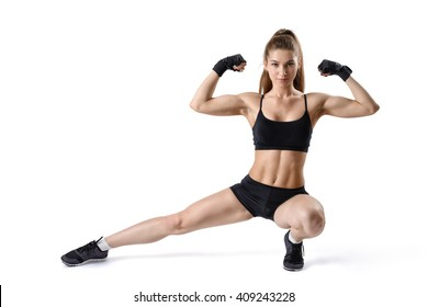 Portrait of strong muscular woman flexing her biceps and stretching leg. Cutout fitness girl.
