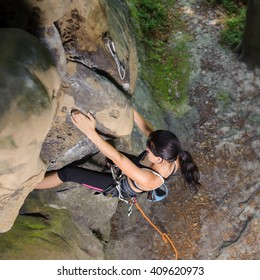 Portrait of strong sporty fit female is climbing the big natural boulder in summer time. Top view. Accent on hands. Healthy lifestyle concept. 1x1