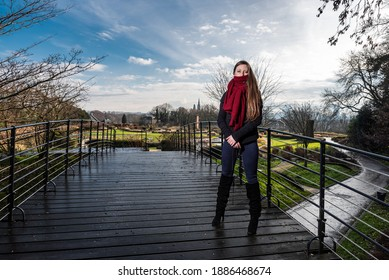 Portrait of a strong thirty year old woman, wearing winter clothes , standing on a pedestrian bridge in a park in winter