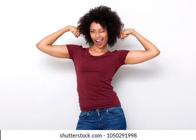 Portrait of strong young african woman flexing both arms muscles and winking on white background